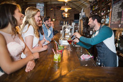 Cheerful bartender interacting with customers while making drink Stock Photo
