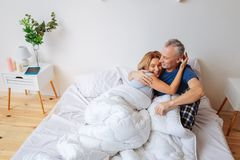 Cheerful beaming wife hugging her strong supportive man. Beaming wife. Cheerful beaming wife hugging her strong supportive men in the bedroom stock image