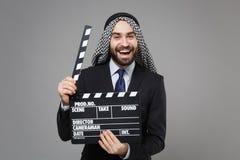 Cheerful bearded arabian muslim businessman in keffiyeh kafiya ring igal agal suit isolated on gray background