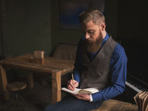 Cheerful bearded author is writing a poem Royalty Free Stock Image
