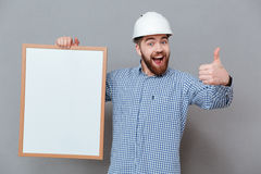 Cheerful bearded builder holding copyspace board. Photo of cheerful bearded builder holding copyspace board and make thumbs up gesture standing over grey Stock Photography