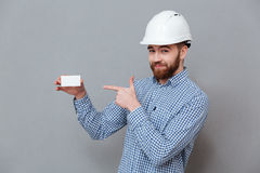 Cheerful bearded builder holding copyspace business card. Photo of cheerful bearded builder holding copyspace business card and pointing standing over grey Stock Image