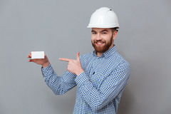 Cheerful bearded builder holding copyspace business card. Picture of cheerful bearded builder holding copyspace business card and pointing standing over grey Stock Images