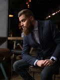 Cheerful bearded businessman is waiting in cafe Royalty Free Stock Photo