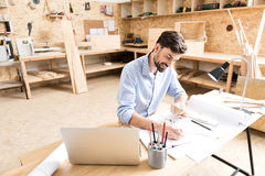 Cheerful bearded craftsman working on new manufacture design in workshop Royalty Free Stock Photo