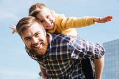 Cheerful bearded father having fun with his little son. Picture of cheerful bearded father having fun with his little son outdoors in the park. Looking at camera Royalty Free Stock Photos