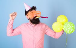 Cheerful bearded man in birthday cap blowing party whistle, fun time, happiness concept. Artist in big crazy glasses. Holding colorful balloons. Man with Royalty Free Stock Photo