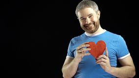 Cheerful bearded man in blue tshirt holds one red heart shape. Love, single, romance, dating, relationship concepts.  Royalty Free Stock Image