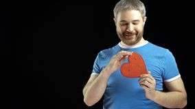 Cheerful bearded man in blue tshirt holds one red heart shape stock footage