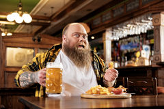 Cheerful bearded man eating chips in bar Stock Photography