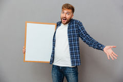 Cheerful bearded man holding blank board and shrugging shoulders Stock Photo