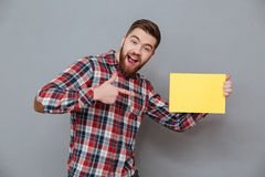 Cheerful bearded man holding copyspace blank. Picture of cheerful bearded man holding copyspace blank standing over grey background and pointing Royalty Free Stock Photo