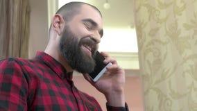 Cheerful bearded man with phone.