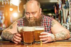 Cheerful bearded man placing glasses of beer Royalty Free Stock Image