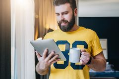 Cheerful bearded man stands and using tablet computer. Guy laughs looking screen of digital tablet while drinking coffee. Young cheerful bearded man stands in Stock Photo