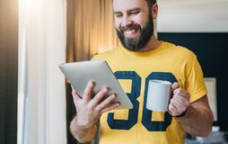Cheerful bearded man stands and using tablet computer. Guy laughs looking screen of digital tablet while drinking coffee. Young cheerful bearded man stands in Royalty Free Stock Photos