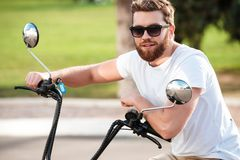 Cheerful bearded man in sunglasses sitting on modern motorbike Royalty Free Stock Images