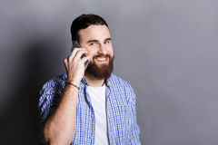 Cheerful bearded man talking on phone Royalty Free Stock Photos