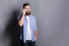 Cheerful bearded man talking on phone Stock Image