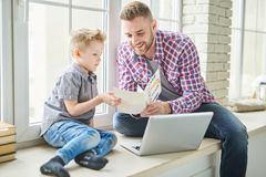 Celebrating Fathers Day with Little Son. Cheerful bearded men wearing jeans and checked shirt sitting on windowsill and reading greeting card given by his cute royalty free stock images