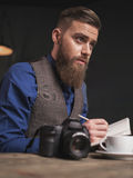 Cheerful bearded photographer is doing his work Royalty Free Stock Image