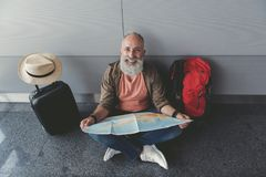 Hilarious smiling old man holding map. Cheerful bearded tourist is sitting in waiting hall. He choosing future route for trip and looking at camera with smile Stock Photos