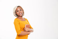 Cheerful beautiful african american woman standing and holding a book Royalty Free Stock Photo