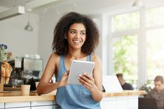 Cheerful beautiful african female student resting in cafe smiling looking in side holding tablet. Royalty Free Stock Photos