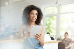 Cheerful beautiful african female student resting in cafe smiling looking in side holding tablet. Stock Photo