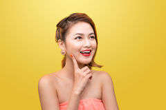 Cheerful beautiful asian young woman with charming smile over ye Royalty Free Stock Photo