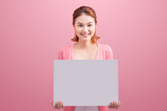 Cheerful beautiful asian young woman holding blank board on pink Royalty Free Stock Images
