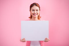 Cheerful beautiful asian young woman holding blank board on pink background.  Stock Photography