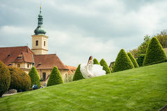 Cheerful beautiful bride is spinning round on the meadow at the background of the old buildings of Prague. Royalty Free Stock Photography