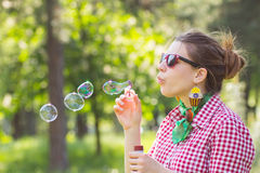 Cheerful beautiful brunette girl in glasses blowing soap bubbles Royalty Free Stock Image