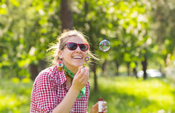 Cheerful beautiful brunette girl in glasses blowing soap bubbles Stock Images