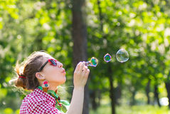 Cheerful beautiful brunette girl in glasses blowing soap bubbles Stock Photo