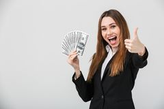 Cheerful beautiful brunette lady showing thumb up and dollars while looking camera isolated Stock Photos