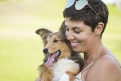 Cheerful beautiful caucasian woman carying a nice pet shetland dog with love and friendship. best friends forever concept with