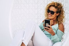 Free Cheerful Beautiful Curly Young Adult Woman Use Mobile Phone Outdoor Sit Down On A White Garden Elegant Chair -smile And Enjoy The Royalty Free Stock Images - 160272539
