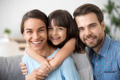 Cheerful beautiful family of three embracing laughing looking at stock photography