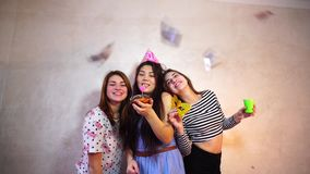 Lovely friendly girls celebrate birthday of their female friends and have fun standing on background of light wall in. Cheerful and beautiful female friends stock video footage