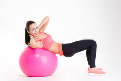 Cheerful beautiful fitness girl training abdominal muscles using fitball Stock Photography
