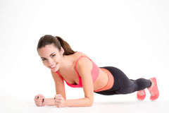 Cheerful beautiful fitness woman doing plank exercise Stock Image