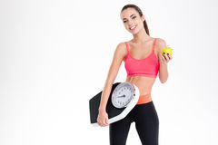 Cheerful beautiful fitness woman holding weighing scale and yellow apple Stock Photography