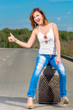 Cheerful beautiful girl catches passing car Royalty Free Stock Photo