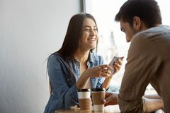 Cheerful beautiful girl with dark hair sits in cafe on date, laughing and telling funny stories from life to her Royalty Free Stock Photography