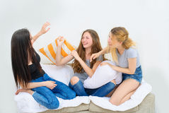 Cheerful beautiful girl friends fighting on the pillows. Active entertainment. Portrait of three happy pretty young women at home having fun Stock Images