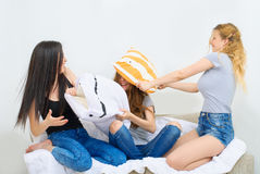 Cheerful beautiful girl friends fighting on the pillows. Active entertainment. Royalty Free Stock Photos