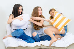 Cheerful beautiful girl friends fighting on the pillows. Active entertainment. Portrait of three happy pretty young women at home having fun Royalty Free Stock Photo