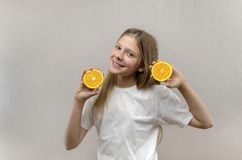Cheerful beautiful girl holds in halves of orange halves. Positive emotions. Healthy food. Veggie and Vegan stock photo